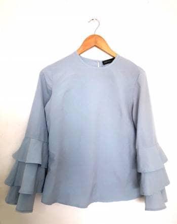 Blusa azul cielo de mangas anchas.